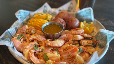 a basket of shrimp, corn and potatoes with a beer