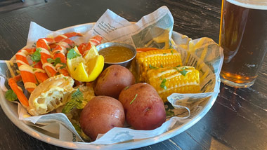 crab legs, corn and potatoes with a beer