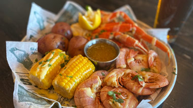 basket of crab, shrimp, corn and potatoes with a beer
